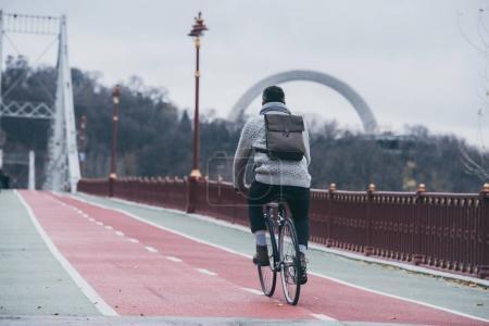 stylish man riding bicycle on pedestrian bridge on autumn day
