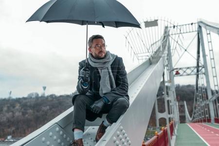 lonely adult man with umbrella sitting on bridge construction