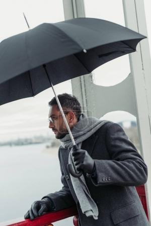 stylish adult man in scarf and coat with umbrella on bridge