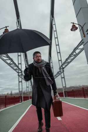 stylish adult man with umbrella and luggage walking by pedestrian bridge