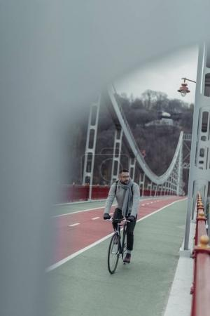 handsome adult man riding bicycle on pedestrian bridge