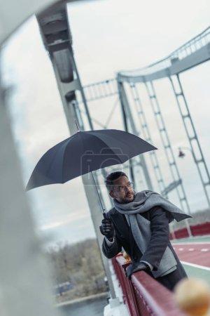 stylish adult man in scarf with umbrella on bridge
