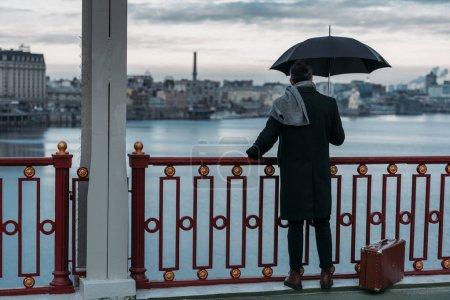 Photo pour Vue arrière de l'homme seul avec parapluie et valise debout sur le pont - image libre de droit