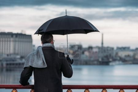 Photo pour Vue arrière de l'homme seul avec parapluie debout sur le pont - image libre de droit