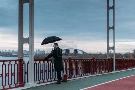 Photo pour Homme solitaire élégant avec valise debout sur le pont et de parapluie - image libre de droit