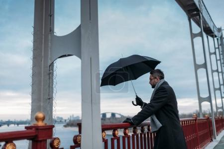 handsome lonely man with umbrella standing on bridge