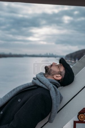 thoughtful middle aged man leaning on bridge construction
