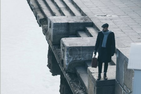 high angle view of adult man with suitcase standing on river shore