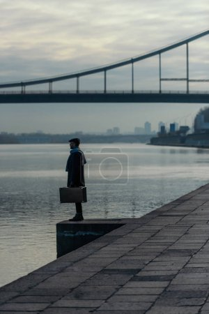 handsome adult man in coat with suitcase standing on river shore