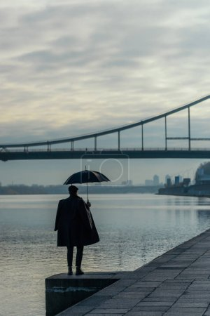stylish man with umbrella standing on river shore