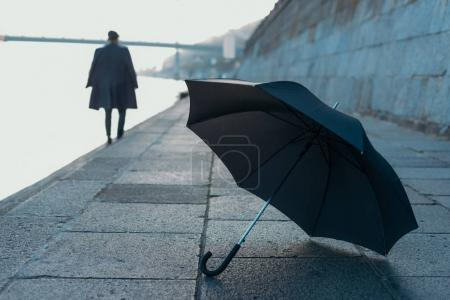 umbrella lying on river shore while man walking blurred on background