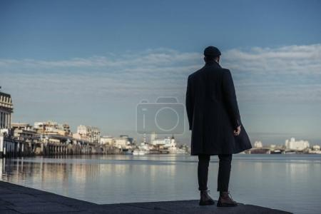 Photo for Lonely man standing on river coast and looking away - Royalty Free Image
