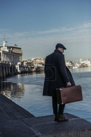 stylish adult man in coat with suitcase standing on river shore