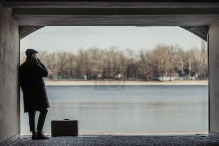 handsome adult man with suitcase smoking in tunnel in front of river shore
