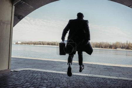 stylish man with baggage running out tunnel to river shore
