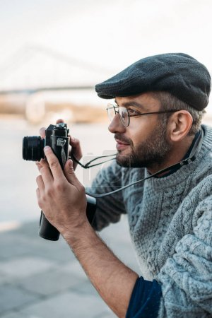 stylish adult man with vintage film camera outdoors