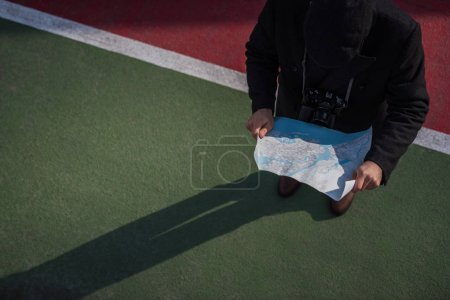 high angle view of man in coat and cap standing with map