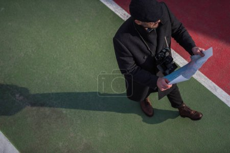 high angle view of traveller in coat and cap walking with map