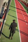 stylish middle aged man walking by pedestrian bridge