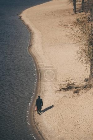 high angle view of man in coat with suitcase walking by sandy beach in autumn
