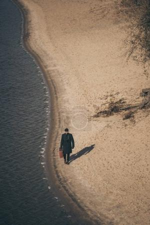 high angle view of man with luggage walking by sandy beach in autumn