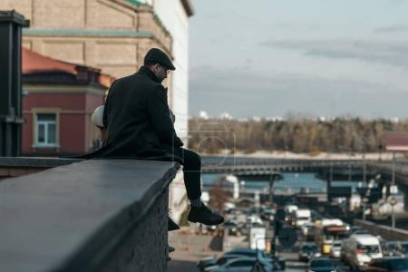 Photo for Stylish middle aged man sitting on roof of building - Royalty Free Image