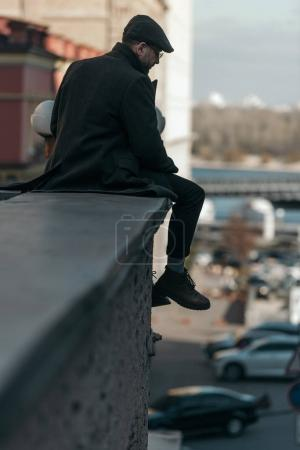handsome middle aged man sitting on roof of building