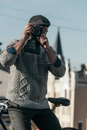 stylish man with vintage film camera in old town