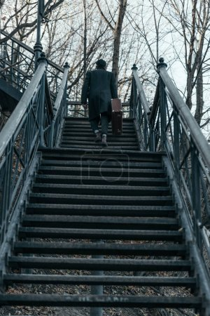 back view of man with suitcase going upstairs