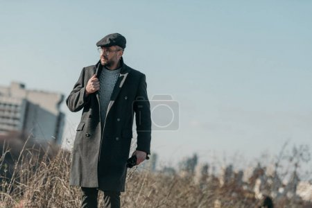 handsome middle aged man in coat walking outdoors