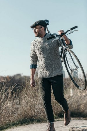 Photo pour Bel homme adulte transportant le vélo sur route rurale - image libre de droit