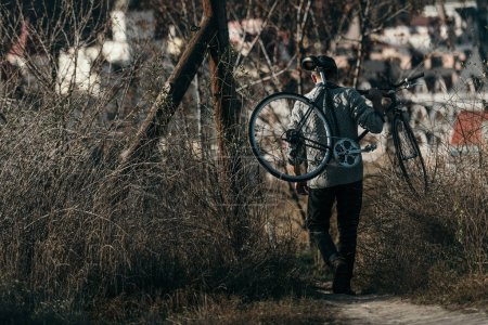 stylish adult man carrying bicycle on rural road