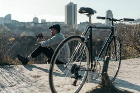 handsome adult man with vintage film camera and bicycle sitting on rural road