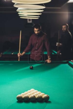 handsome men playing in russian pool at bar