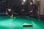 successful handsome man playing in pool at bar with friends