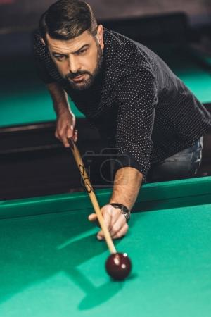 front view of handsome man playing in pool at billiard bar