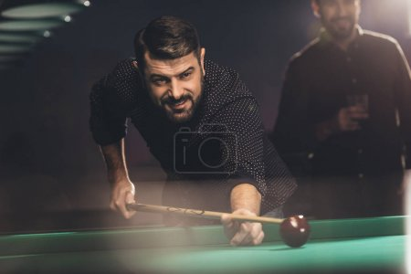 successful man playing in pool at bar with friend