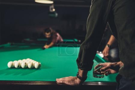 cropped image of man holding glass with drinks infront of pool table at bar