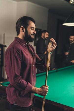 handsome man rubbing cue with chalk at bar with friends