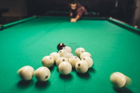 man playing in russian billiard at bar