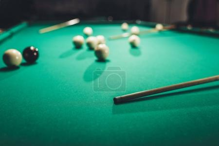 green billiard table with russian pool balls and cues