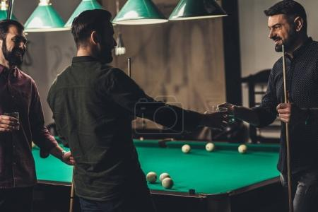 company of successful handsome men with drink beside pool table at bar