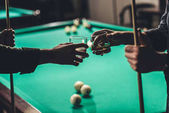 cropped image of male hands with cues and glasses with alcohol infront of billiard table at bar