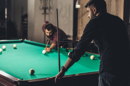 company of successful handsome men playing in pool at bar