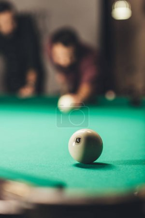 front view of men playing in russian pool. selective focus on ball