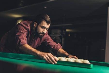 handsome man forming triangle of russian pool balls at bar