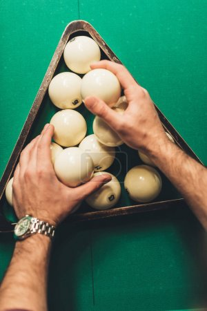 cropped image of man forming triangle of russian pool balls