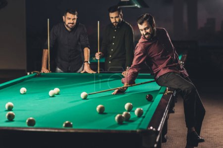 Photo for Company of young successful handsome men playing in russian pool at bar - Royalty Free Image