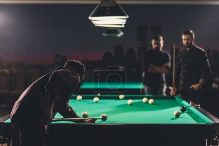 company of successful men playing in russian pool at bar