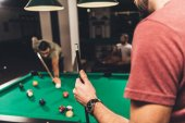 caucasian man beside billiard table at bar with friends